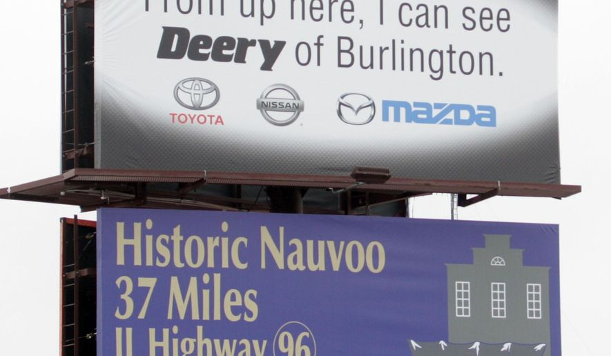 A mannequin sits on top of a Deery Brothers billboard on the southbound side of Highway 61, Thursday, Jan. 22, 2015 near Mediapolis, Iowa. The mannequin is so life like that it has fooled many drivers into calling 911 believing their is a real person on top of the sign. (AP Photo/The Hawk Eye, Josh Newell) MANDATORY CREDIT