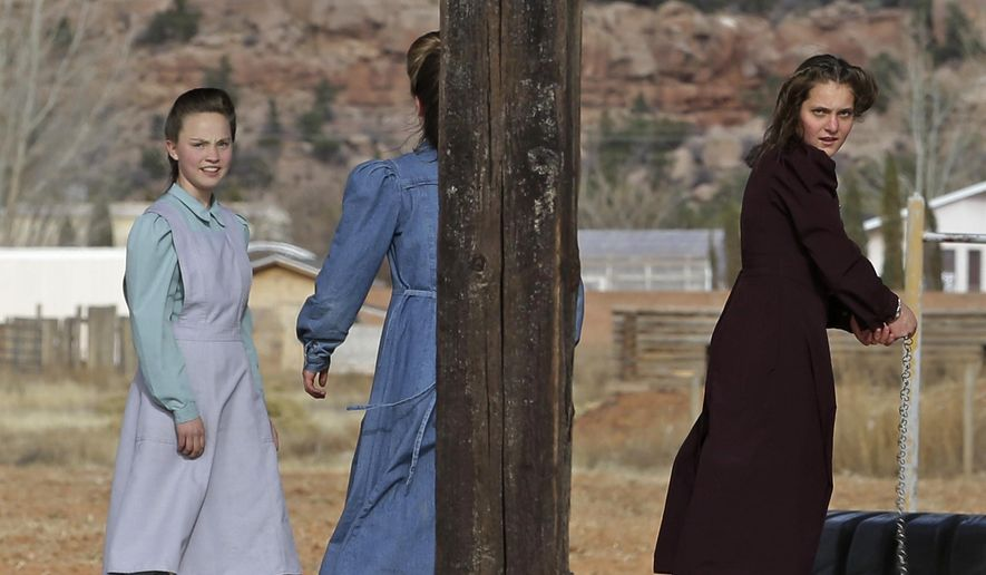 In this Dec. 16, 2014 photo, girls stand in a playground in Colorado City, Ariz. The sister cities of Hildale, Utah, and Colorado City, once run by polygamist leader Warren Jeffs, are split between loyalists who still believe he is a victim of religious persecution and defectors who are embracing government efforts to pull the town into modern society. (AP Photo/Rick Bowmer)