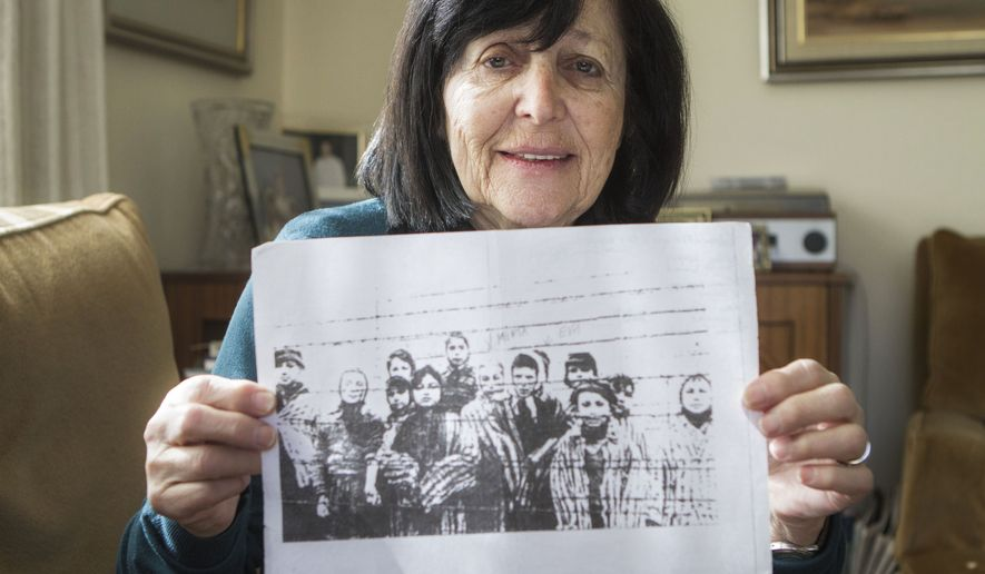 In this photo taken Thursday, Jan. 22, 2015, Marta Wise holds a famous black-and-white photo, taken by the Russian liberators of Auschwitz, showing her, center, with about a dozen children in rags standing behind a row of barbed wire that has become one of the most iconic images of the Holocaust, as she poses for a portrait in her house in Jerusalem. Wise was ill and emaciated when she heard the distant sound the soldiers marching toward Auschwitz. The 10-year-old Slovakian Jew assumed it was German troops coming to get her but once she saw the red stars on their uniforms she realized they were Russian. Her nightmare was over. She was liberated. (AP Photo/Dan Balilty)