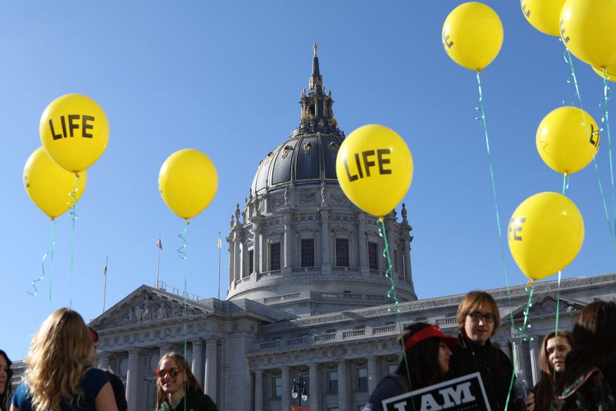 """Members of the St. Rose of Lima Parish of Paso Robles Calif. arrive to the """"Walk for Life"""" rally and march in San Francisco on Saturday, Jan. 24, 2015. Thousands of abortion opponents gathered at Civic Center Plaza in front of City Hall for the 11th annual event before marching down Market Street to Justin Herman Plaza. (AP Photo/Alex Washburn)"""
