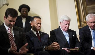 In this Jan. 13, 2015 file photo, Former Atlanta fire chief Kelvin Cochran, third from right, observes a moment of prayer as religious groups rally to support him following his termination in Atlanta. (AP Photo/David Goldman/File) **FILE**
