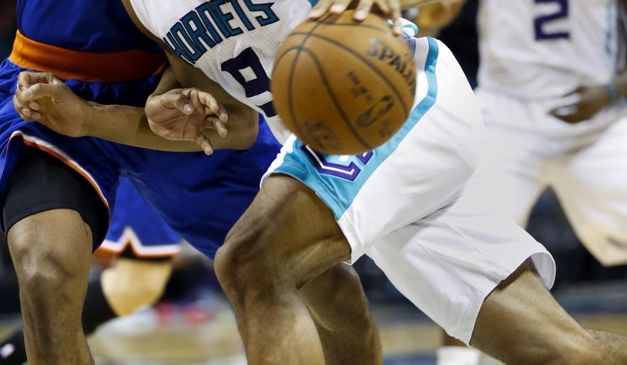Charlotte Hornets forward Gerald Henderson, right, drives into New York Knicks forward Lance Thomas in the first half of an NBA basketball game Saturday, Jan. 24, 2015, in Charlotte, N.C. (AP Photo/Nell Redmond)