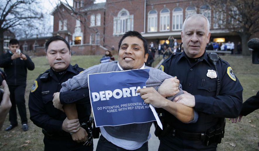 Marco Malagon is removed from the venue by Des Moines police officers after protesting during former Texas Gov. Rick Perry's speech at the Freedom Summit, Saturday, Jan. 24, 2015, in Des Moines, Iowa. (AP Photo/Charlie Neibergall)