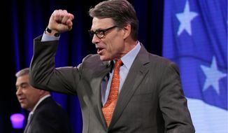 Former Texas Gov. Rick Perry pumps his fist as he walks on stage during the Freedom Summit, Saturday, Jan. 24, 2015, in Des Moines, Iowa. (AP Photo/Charlie Neibergall)