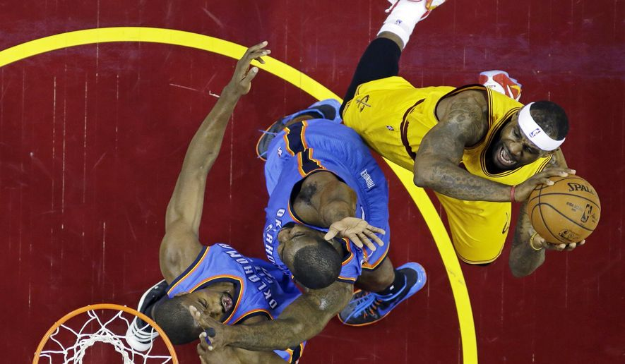 Cleveland Cavaliers' LeBron James, right, shoots over Oklahoma City Thunder's Kendrick Perkins, center, and Serge Ibaka in the first half of an NBA basketball game Sunday, Jan. 25, 2015, in Cleveland. (AP Photo/Mark Duncan)