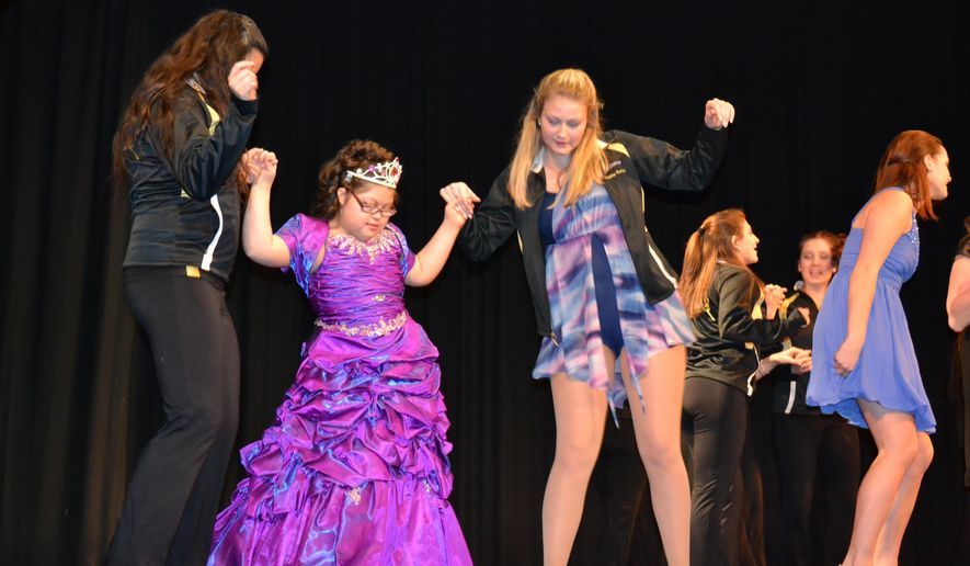 """ADVANCE FOR USE SUNDAY, JAN. 25, 2015, AND THEREAFTER- In this Jan. 17, 2015, photo, Charles Town Middle School student and Miss Extraordinary contestant Gabriela Bautista, center, dances with her """"buddies"""" Kendra Jalbert and Sophia Runion from Jefferson High School's Charisma dance team during the third annual Miss Extraordinary Special Needs Pageant in Shenandoah Junction, W.Va. The pageant showcased the talents and winning personalities of Jefferson students with special needs. Mary Stortstrom (AP Photo/The Journal, Mary Stortstrom)"""