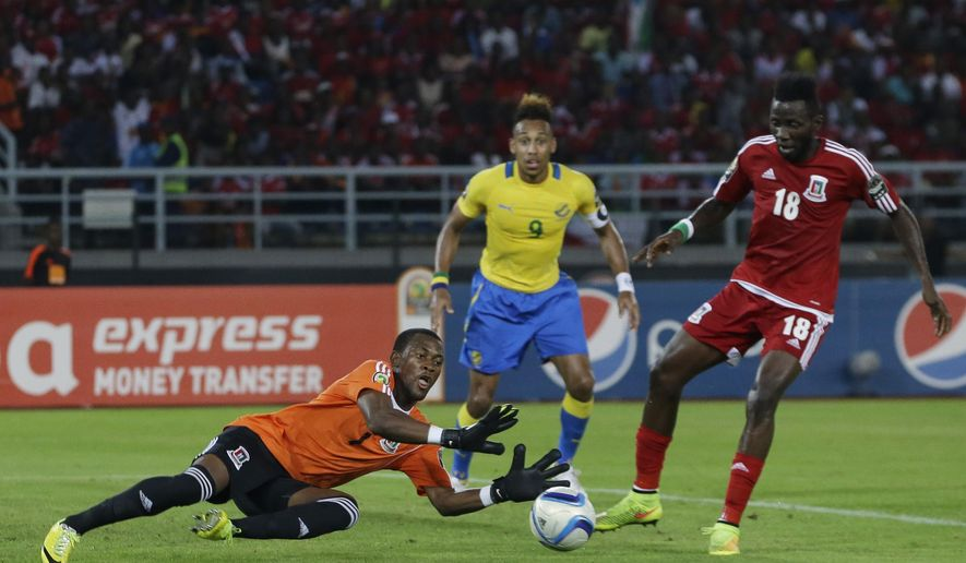 Equatorial Guinea's goalkeeper Felipe Ovono, dives for the ball as teammate Viera Ellong Doualla, right, and Gabon's Pierre Aubameyang, center, watch during their African Cup of Nations Group A soccer match in Bata, Equatorial Guinea, Sunday, Jan. 25, 2015. (AP Photo/Themba Hadebe)
