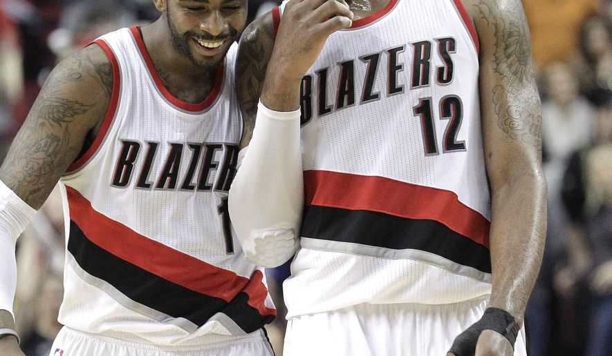 Portland Trail Blazers forward LaMarcus Aldridge, right, and teammate Dorell Wright chat in the final seconds of an NBA basketball game against the Washington Wizards in Portland, Ore., Saturday, Jan. 24, 2015. Aldridge led the Trail Blazers with 26 points as they defeated the Wizards 103-96. (AP Photo/Don Ryan)