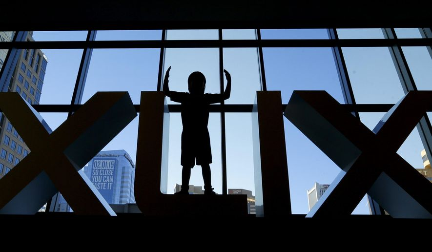 Diego Santa Cruz, 8, from Phoenix, poses for a photo in a set of Roman numerals at the Super Bowl XLIX NFL Experience Saturday, Jan. 24, 2015, in Phoenix. (AP Photo/Charlie Riedel)