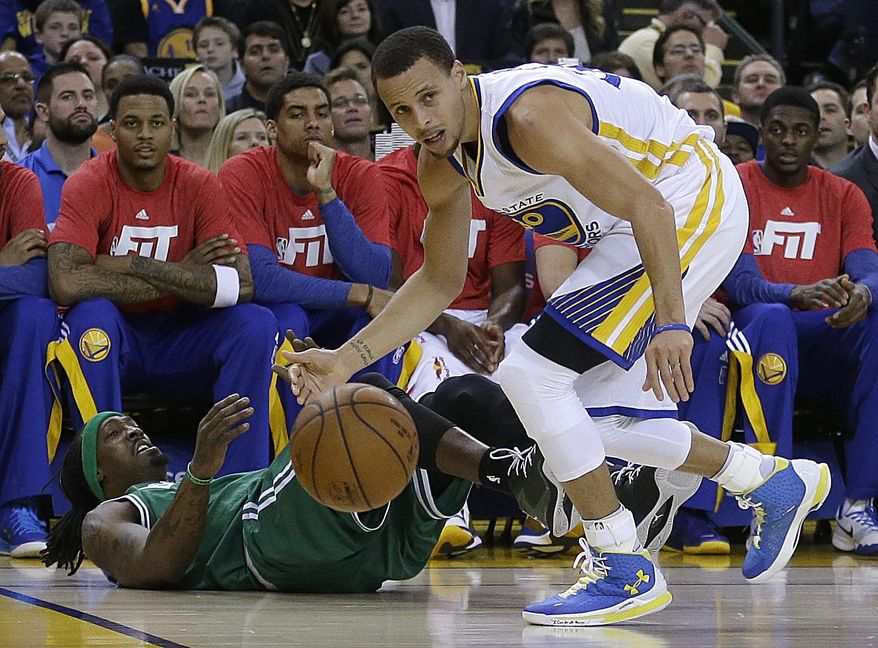 Golden State Warriors' Stephen Curry, right, recovers the ball as Boston Celtics' Gerald Wallace falls during the first half of an NBA basketball game, Sunday, Jan. 25, 2015, in Oakland, Calif. (AP Photo/Ben Margot)
