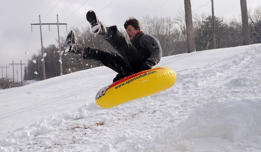Matthew Schiccatano rides on a snow tube as he launches off of a make shift snow jump on Saturday, Jan. 24, 2015 on the Shamokin, Pa. Area Elementary School campus. (AP Photo/The News-Item, Mike Staugaitis)