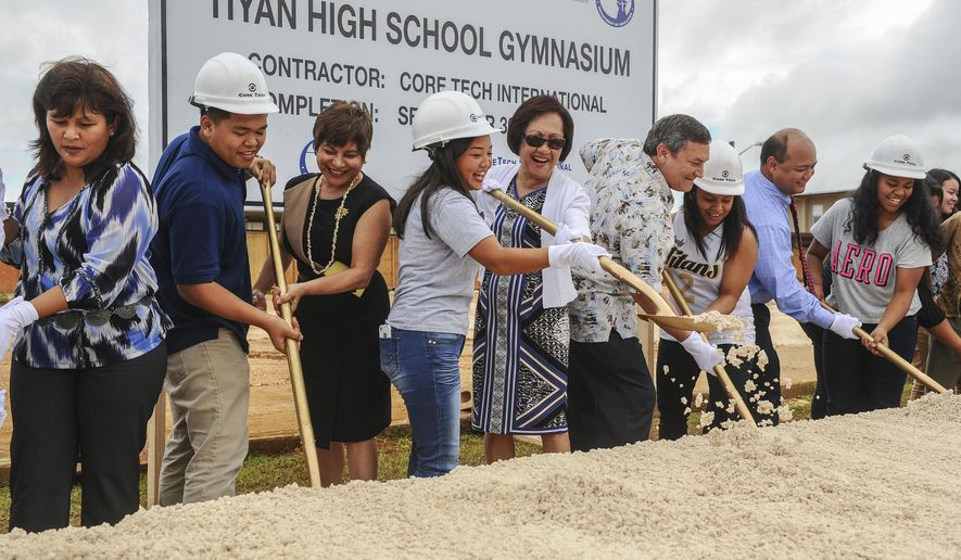 ADVANCE FOR SUNDAY JAN. 25 AND THEREAFTER - In this photo taken Jan. 22, 2015, Associated Body of Students President Janay Masga, center wearing hard hat, and Guam Education Board Vice Chairperson Maria Gutierrez share a shovel as they and others turn soil during the ceremonial groundbreaking of the Tiyan High School gymnasium in Hagatna, Guam.  Students at the high school will soon have a new multimillion-dollar gym. The school, which opened in August, broke ground on a new gymnasium, slated to open in September. (AP Photo/Pacific Daily News, Rick Cruz)