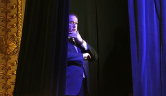 Former Arkansas Gov. Mike Huckabee waits backstage before speaking during the Freedom Summit in Des Moines, Iowa.  (AP Photo/Charlie Neibergall)