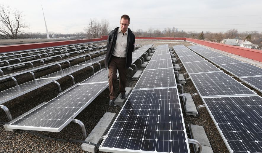In a Friday, Jan. 23, 2015 photo, Joe Bowling, supervisor for the Englewood Solar Project, looks over solar panels on the roof of the Englewood Christian Church in Indianapolis. Solar energy supporters are pushing back against a bill backed by Indiana's utilities that would change how much credit owners of small-scale solar installations get for the power they generate. (AP Photo/The Indianapolis Star, Mike Fender)  NO SALES