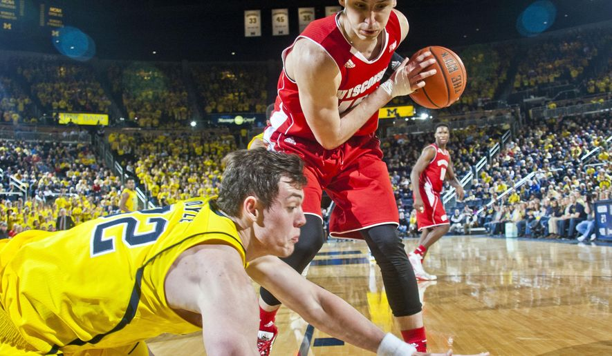 Wisconsin forward Sam Dekker, top, grabs the ball away from Michigan forward Ricky Doyle during the second half of an NCAA college basketball game in Ann Arbor, Mich., Saturday, Jan. 24, 2015. Wisconsin won 69-64 in overtime. (AP Photo/Tony Ding)