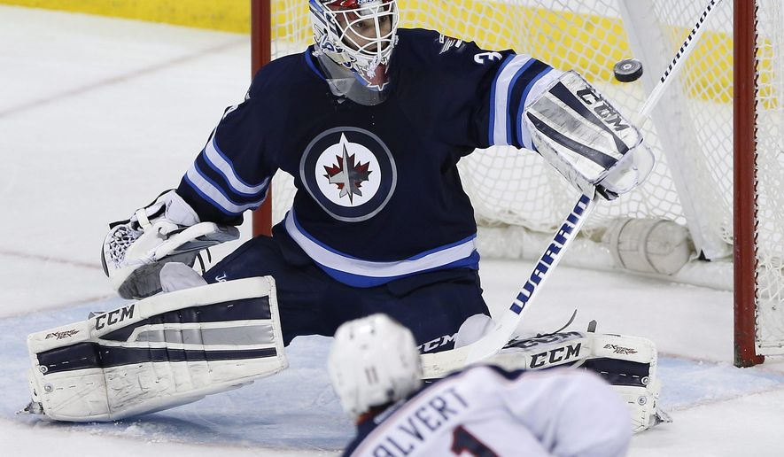Winnipeg Jets goaltender Michael Hutchinson gets a blocker on a shot by Columbus Blue Jackets' Matt Calvert (11) during the third period of an NHL hockey game Wednesday, Jan. 21, 2015, in Winnipeg, Manitoba. (AP Photo/The Canadian Press, Jason Woods)