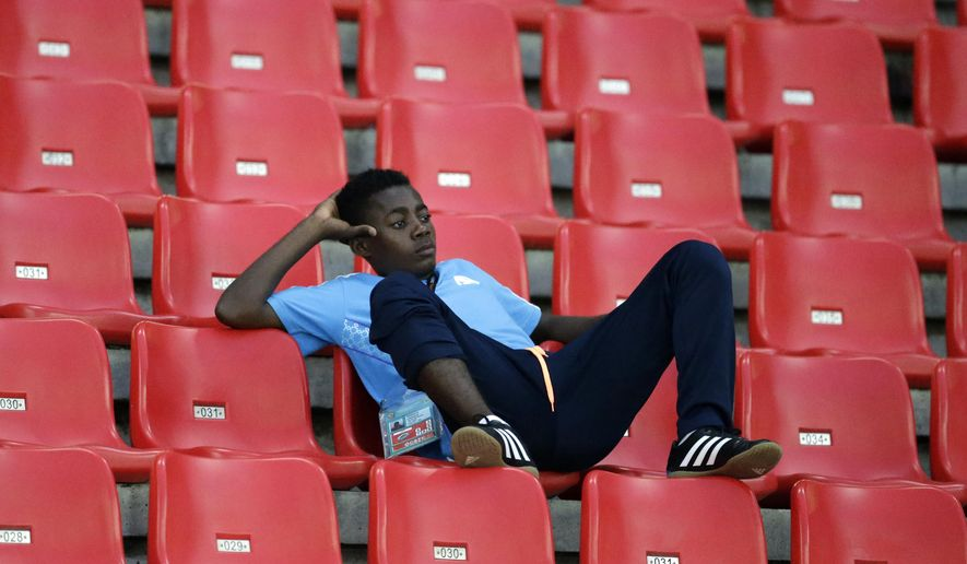 A volunteer watches the African Cup of Nations Group B soccer match between DR Congo and Tunisia in Bata, Equatorial Guinea, Monday, Jan. 26, 2015. (AP Photo/Themba Hadebe)