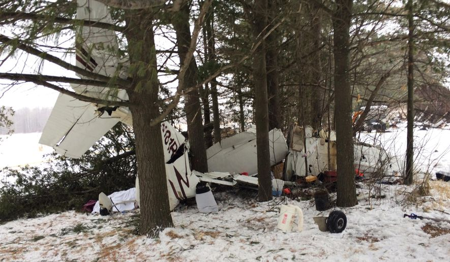 In this photo provided by the Clark County, Wis., sheriff's office is the wreckage of a Cessna 182 that crashed killing one and injuring two Monday, Jan., 26, 2015 in Hoard, Wis., according to the sheriff's office.  Authorities say the plane was trying to make an emergency landing on a road when a wing clipped tree branches causing the plane to crash into a ditch. (AP Photo/Clark County Sheriff's Office)