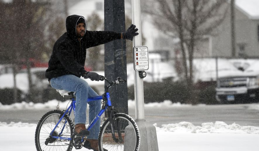 A cyclist waits for the traffic light in the snow at Bank and Howard streets in New London, Conn., Monday, Jan. 26 2015. (AP Photo/The Day, Sean D. Elliot)