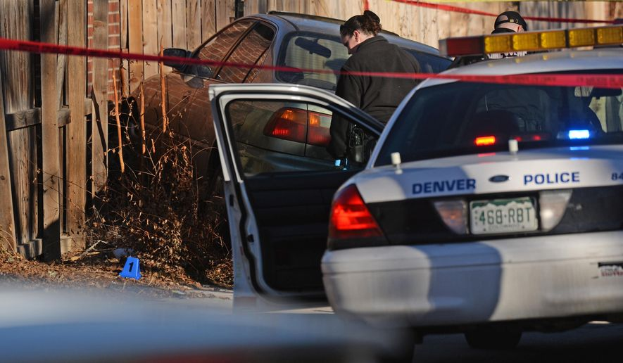 Denver police shot and killed a female suspect early Monday, Jan. 26, 2015, after they said she drove a stolen car at officers, hitting one of them in the leg. Neighbors described the driver as a teenager. (AP Photo/The Denver Post, RJ Sangosti)