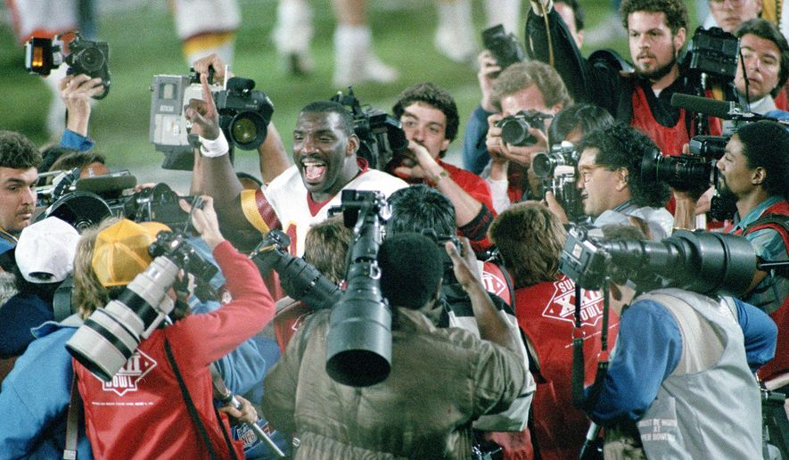 FILE - In this Feb. 1, 1988, file photo, Washington Redskins quarterback Doug Williams is surrounded by members of the media after he led the Redskins to a 42-10 victory over the Denver Broncos in Super Bowl XXII in San Diego, Ca. The history of Super Bowl Media Day, and mandatory player availability, has played a key role in making the Super Bowl most-watched NFL TV program. (AP Photo/File)