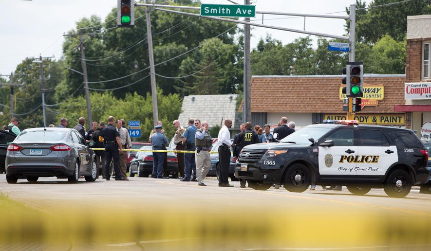 In a Wednesday, July 30, 2014 photo, authorities are gathered at the scene of shooting in which a Mendota Heights police officer was killed in West St. Paul, Minn. Alice Fitch, the mother of Brian Fitch who is currently on trial in Stearns County, is apologizing to the family of Mendota Heights Officer Scott Patrick. (AP Photo/MPR News, Jennifer Simonson)