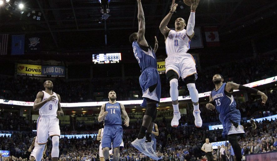 Oklahoma City Thunder guard Russell Westbrook (0) shoots in front of teammate Serge Ibaka (9), and Minnesota Timberwolves center Nikola Pekovic (14), center Gorgui Dieng (5) and guard Mo Williams (25) in the first quarter of an NBA basketball game in Oklahoma City, Monday, Jan. 26, 2015. (AP Photo/Sue Ogrocki)