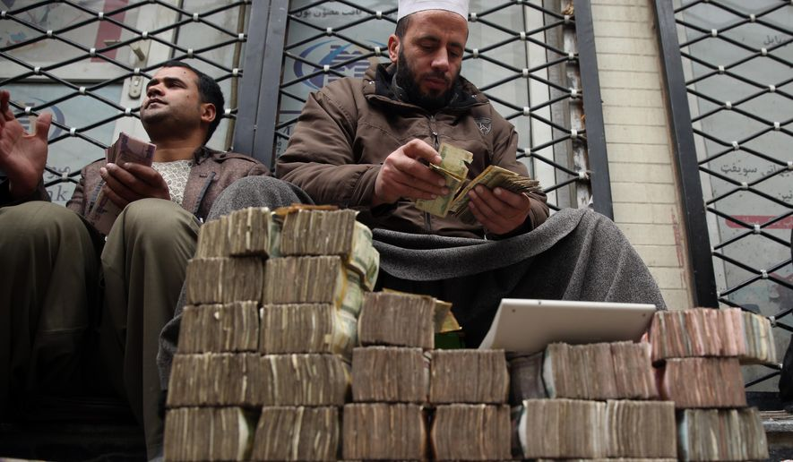 FILE - In this Monday, Jan. 12, 2015 file photo, An Afghan money changer, right, counts a pile of currency at the Money and Exchange Market in Kabul. Afghanistan's fragile economy has lost around a third of its value in the past year as the international military and aid organizations that poured in cash for more than a decade have drastically scaled back after U.S. President Barack Obama declared an end to the 13-year war against the Taliban _ leaving the government struggling for funds and key sectors lacking investment, economists, analysts and officials said. (AP Photo/Massoud Hossaini, FIle)