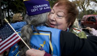 """Donut Dollies"" member Kammy McCleery, is greeted with a hug by a Vietnam War veteran during a parade in Washington, Saturday, Nov. 10, 2007,  in commemoration of the Veterans Day, on Sunday. Donut Dollies served as a recreation worker with the American Red Cross in Vietnam.  (AP Photo/Manuel Balce Ceneta)"