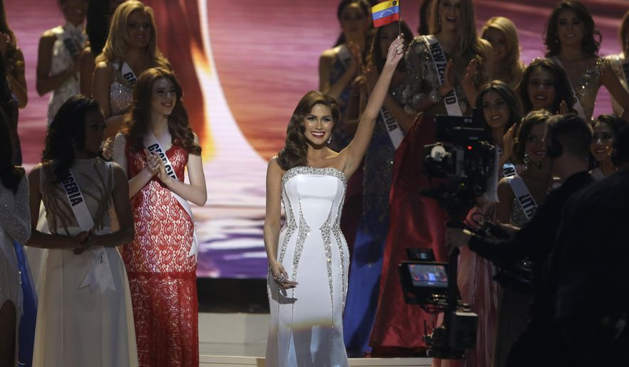 Reigning Miss Universe Gabriela Isler, center, waves to the crowd before crowning the new Miss Universe, Paulina Vega of Colombia, during the Miss Universe pageant in Miami, Sunday, Jan. 25, 2015. (AP Photo/Wilfredo Lee)