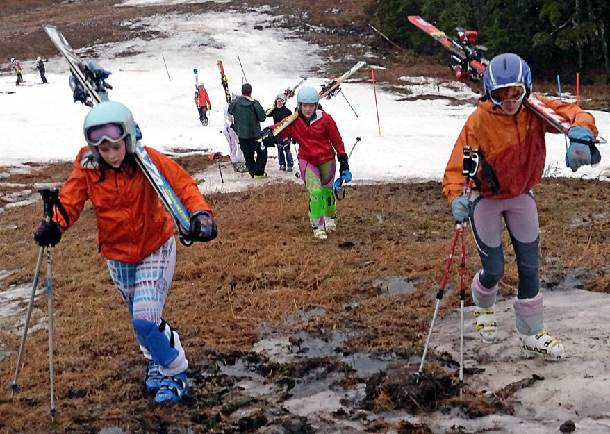 In this Sunday, Jan. 25, 2015, photo, Juneau Ski Team members hike up the slopes of Eaglecrest Ski Area after a practice ski on the small snow-covered portion of the course in Juneau, Alaska. The amount of moisture set a record for the month of January, when 11.29 inches of precipitation fell at the city's airport, the Juneau Empire reported. That broke the previous record of 10.16 inches, set just last year. (AP Photo/The Juneau Empire, Klas Stolpe)