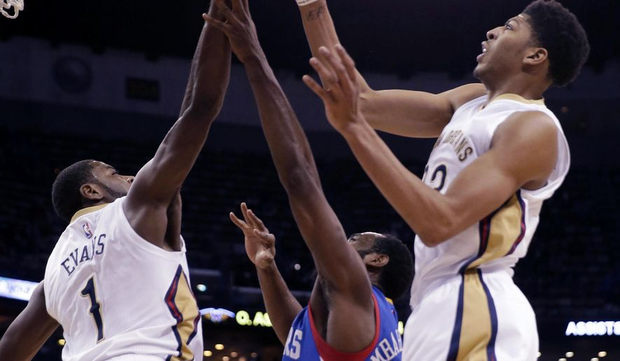 New Orleans Pelicans guard Tyreke Evans (1) and forward Anthony Davis (23) block a shot by Philadelphia 76ers forward Luc Richard Mbah a Moute, center, in the first half of an NBA basketball game in New Orleans, Monday, Jan. 26, 2015. (AP Photo/Gerald Herbert)