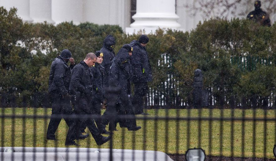 Members of the Secret Service search the grounds of the North Lawn of the White House in Washington, Monday, Jan. 26, 2015. A device, possibly an unmanned aerial drone, was found on the White House grounds during the middle of the night while President Barack Obama and first lady were in India. It was unclear whether their daughters, Sasha and Malia, were at home at the time of the incident with their grandmother, Marian Robinson. (AP Photo/Pablo Martinez Monsivais) **FILE**
