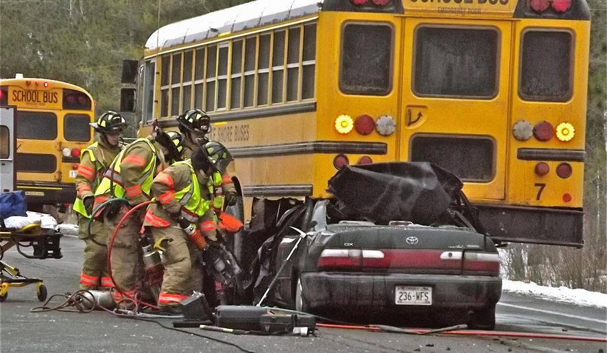 Firefighters use equipment to remove doors and other obstructions so that they can gain access to the driver of a crushed vehicle, which rear-ended a Lake Shore Bus in Ashland, Wis., Tuesday, Jan. 27, 2015. (AP Photo/The Ashland Daily Press, Rick Olivo)