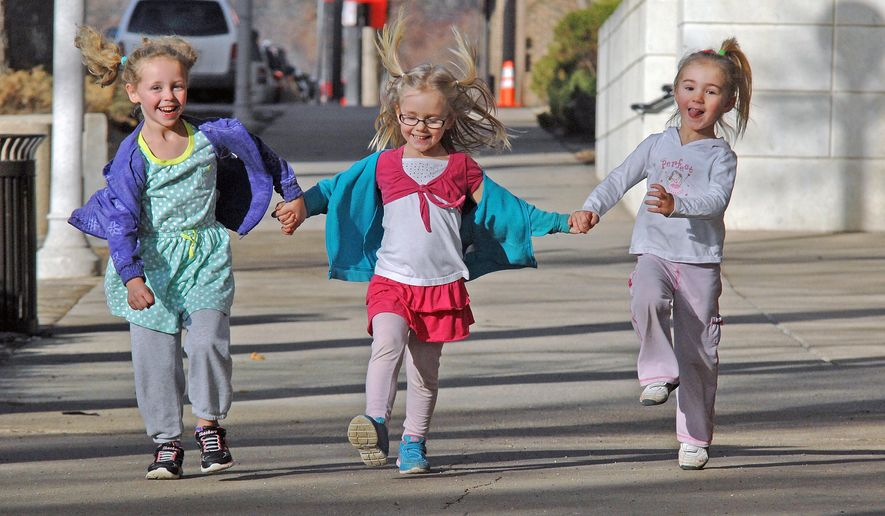 Lainey Swenson, left, Joya Martian, and Anna Martian walk together, Tuesday, Jan. 27, 2015, in Bismarck, N.D. The Bismarck area experienced unusually high temperatures Tuesday. (AP Photo/Tribune, Tom Stromme)