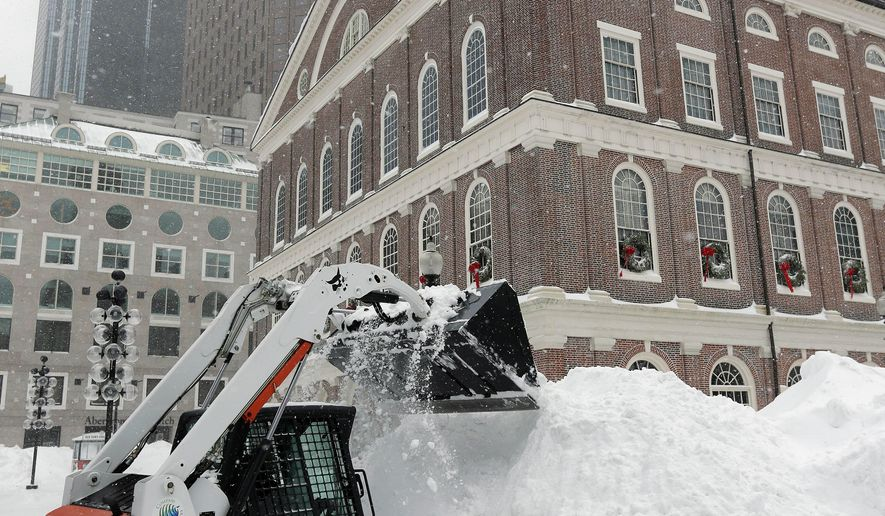 A worker uses a front-end loader to clear snow adjacent to Faneuil Hall, Tuesday, Jan. 27, 2015, in Boston. Massachusetts was pounded by snow and lashed by strong winds early Tuesday as bands of heavy snow left some towns including Sandwich on Cape Cod and Oxford in central Massachusetts reporting more than 18 inches of snow. (AP Photo/Steven Senne)