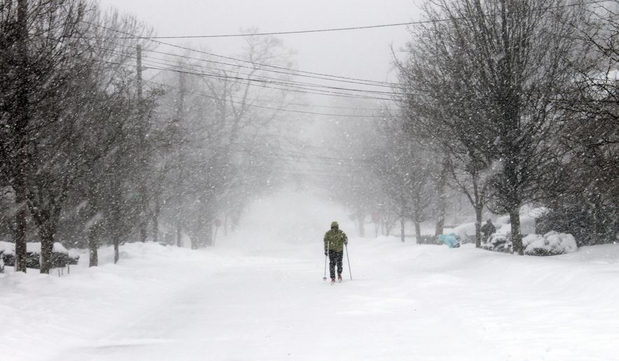 Francisco Fernandez de Alba skis along a recently plowed road during a snowstorm Tuesday, Jan. 27, 2015,  in Providence, R.I. Parts of Rhode Island were buried under nearly two feet of snow by early Tuesday afternoon, and more was on the way as a nasty winter storm with high winds forced the state to a standstill.  (AP Photo/Michelle R. Smith)