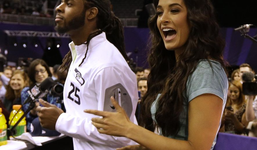 Seattle Seahawks' Richard Sherman dances with Gina Holguim during media day for NFL Super Bowl XLIX football game Tuesday, Jan. 27, 2015, in Phoenix. (AP Photo/David J. Phillip)