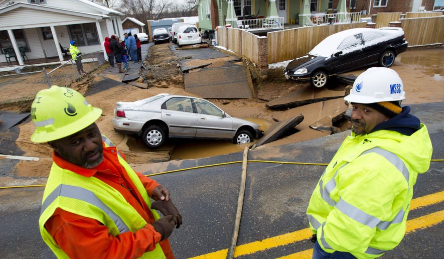 Washington Suburban Sanitary Commission (WSSC) workers are seen at the scene of a car swallowed by a sinkhole that occurred after a water main break in Bladensburg, Md., Tuesday, Jan. 27, 2015. A water main break caused a sinkhole in a suburban Washington, D.C. neighborhood, swallowing up a family's car just after they escaped in Bladensburg Maryland on Tuesday morning. (AP Photo/Jose Luis Magana)