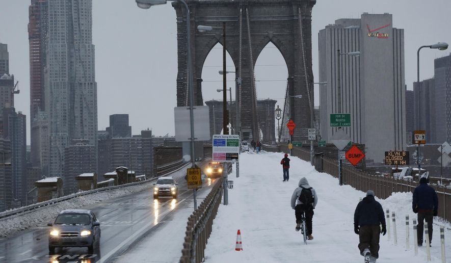 Pedestrians and cars cross the Brooklyn Bridge, Tuesday, Jan. 27, 2015 in New York.  Gov. Andrew Cuomo says a snowstorm-related New York City area travel ban is lifted, except for Suffolk County on Long Island. (AP Photo/Mark Lennihan)