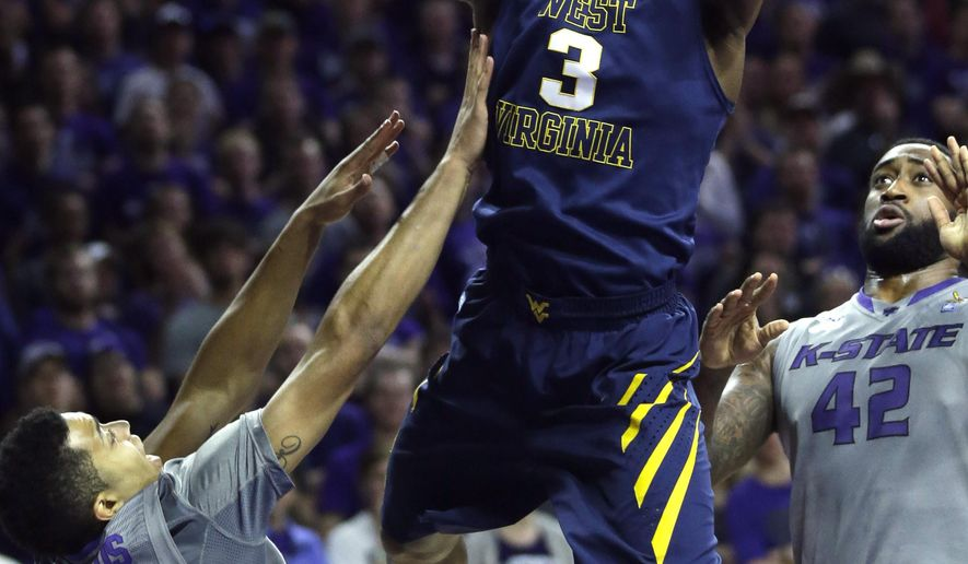 West Virginia guard Juwan Staten (3) shoots between Kansas State guard Justin Edwards (14) and forward Thomas Gipson (42) during the first half of an NCAA college basketball game in Manhattan, Kan., Tuesday, Jan. 27, 2015. (AP Photo/Orlin Wagner)