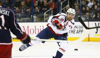 Washington Capitals' Karl Alzner (27) shoots the puck against the Columbus Blue Jackets in the first period of an NHL hockey game, Tuesday, Jan. 27, 2015, in Columbus, Ohio. (AP Photo/Mike Munden)
