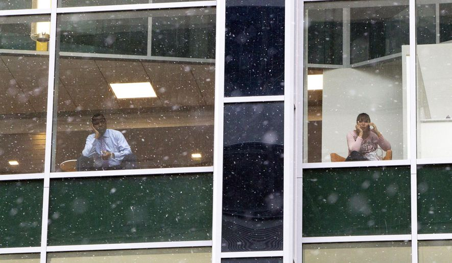 People look out from office building windows as snow falls in downtown Philadelphia, Monday, Jan. 26, 2015. Cities from Boston to New York and Philadelphia were shutting down Monday against a monster storm that could unload up to 3 feet (90 centimeters) of snow on a region of more than 35 million people. (AP Photo/Michael R. Sisak)