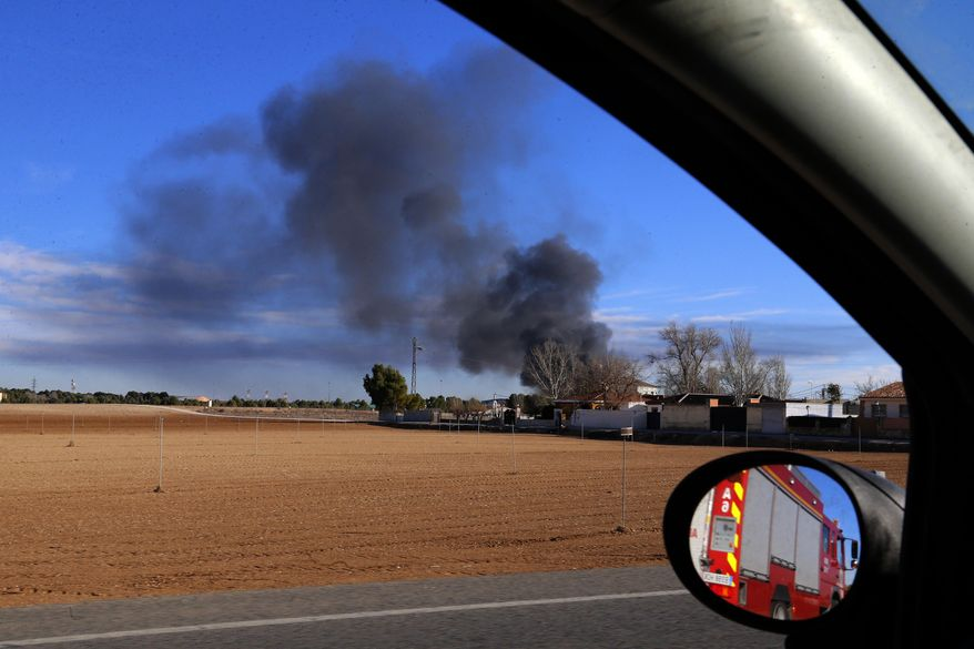Smoke rises from a military base after a plane crash in Albacete, Spain, Monday, Jan. 26, 2015. A Greek F-16 fighter jet crashed into other planes on the ground during NATO training in southeastern Spain Monday, killing at least 10 people, Spain's Defense Ministry said. Another 13 people were injured in the incident at the Los Llanos base, which sent flames and a plume of black smoke billowing into the air, a Defense Ministry official said. (AP Photo/Josema Moreno)