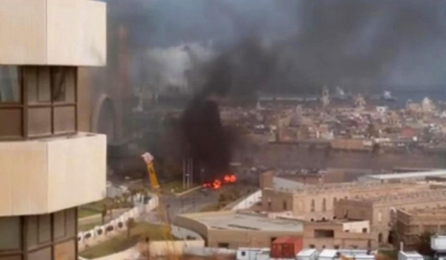 In this image made from video posted by a Libyan blogger, the Cortinthia Hotel is seen under attack in Tripoli, Libya, Tuesday, Jan. 27, 2015. Gunmen stormed the luxury hotel in the Libyan capital of Tripoli on Tuesday, killing several foreigners and guards, officials said. The blogger, @AliTweel, captured the moments shortly after the blast, when flames rose up from outside the hotel, appearing to be from the aftermath of the car bomb. (AP Photo/@AliTweel via AP video)