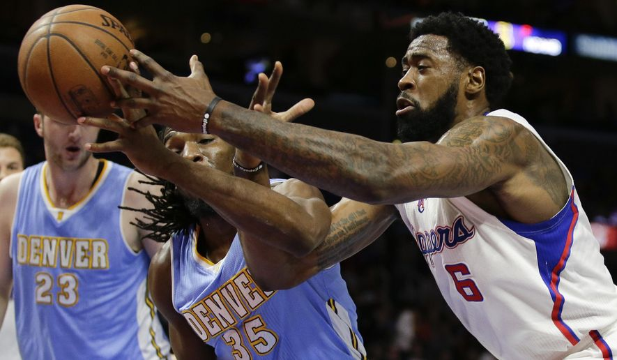 Los Angeles Clippers center DeAndre Jordan, right, reaches past Denver Nuggets forward Kenneth Faried for a rebound during the first half of an NBA basketball game in Los Angeles, Monday, Jan. 26, 2015. (AP Photo/Chris Carlson)