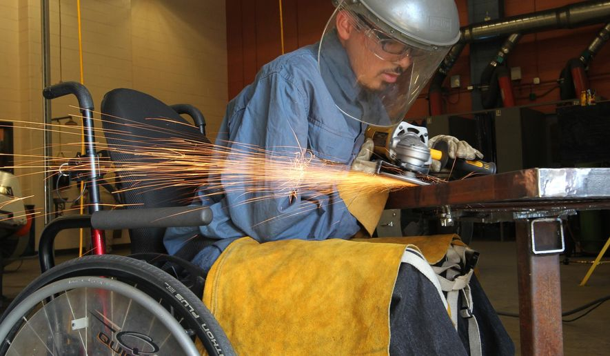 Gabe Simpson, a senior at Texas City High School, grinds a weld on part of a project for a district competition in Shawn Trader's welding class at the high school on Jan. 20, 2015 in Texas City, Texas. Simpson, who has muscular dystrophy, hasn't let his wheelchair keep him from learning the vocation.  (AP Photo/The Galveston County Daily News, Jennifer Reynolds)