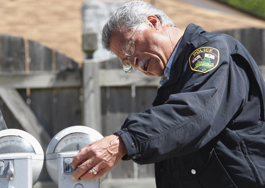 In this May 21, 2008 photo, parking enforcement officer Giovanni Serra looks at a penny parking meter in downtown Sycamore, Ill. The meters in the northern Illinois city may be running out of time. It is one of the few places in the country where penny parking meters are used, but city officials say the more than 300 meters that line downtown streets require timers from a company that no longer makes them. (AP Photo/Daily Chronicle, Eric Sumberg)  CHICAGO TRIBUNE OUT, MANDATORY CREDIT