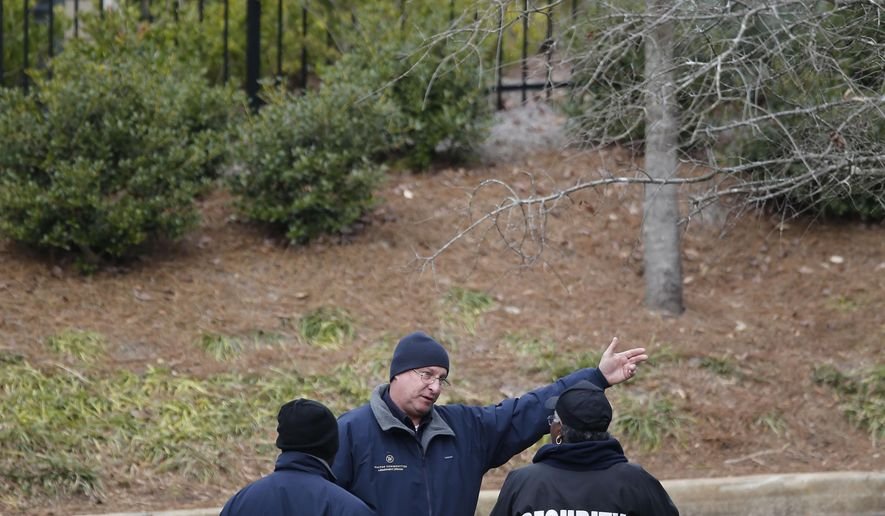 Security personnel guard the main entrance to the Walton Crossing apartments after law enforcement personnel discovered multiple bodies in one of the apartments Tuesday, Jan. 27, 2015, in Austell, Ga. Cobb County Police said in a statement that 35-year-old Kisha S. Holmes of Austell was found dead Tuesday morning along with her 9-month-old daughter, her 4-year-old son and her 10-year-old son. The children's identities have not been released. (AP Photo/David Tulis)