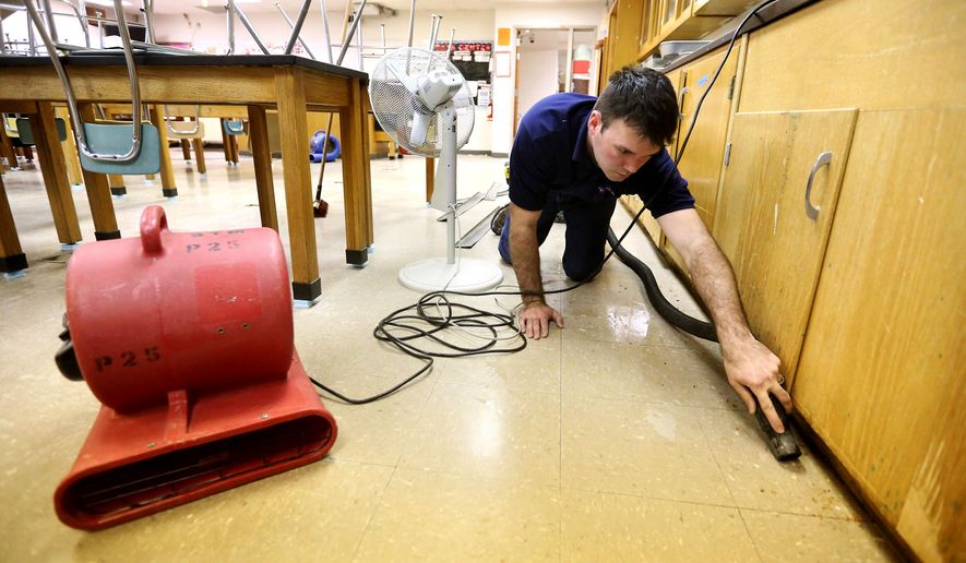 In this photo taken on Monday, Jan. 26, 2015, Shaun Stodden, with Dubuque Area Steamatic, cleans debris at Western Dubuque High School in Epworth, Iowa.  Classes were canceled Monday as a result of vandalism that flooded classrooms at the school. (AP Photo/Telegraph Herald, Jessica Reilly)